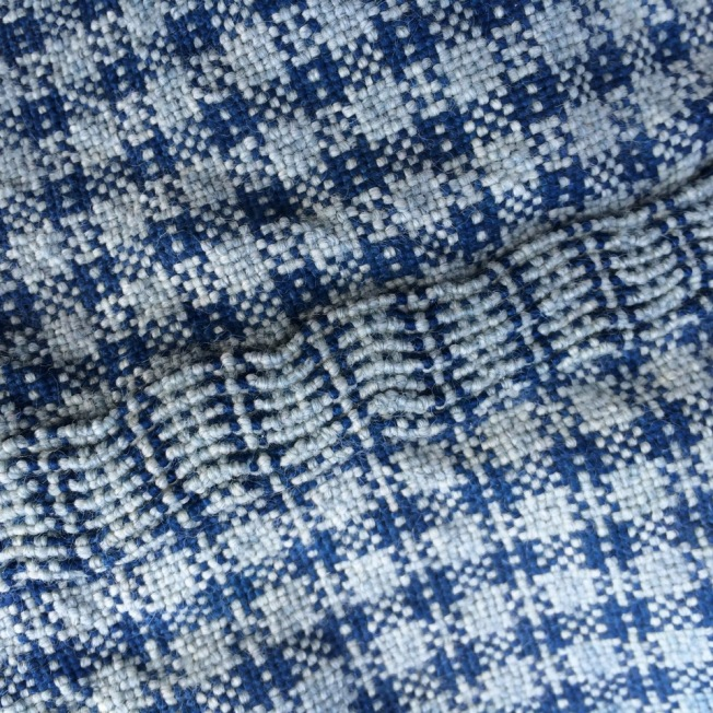 Indigo dye on cotton and wool fabric. The cotton is a deep blue, while the wool is very light, although they were dyed in the same bath.